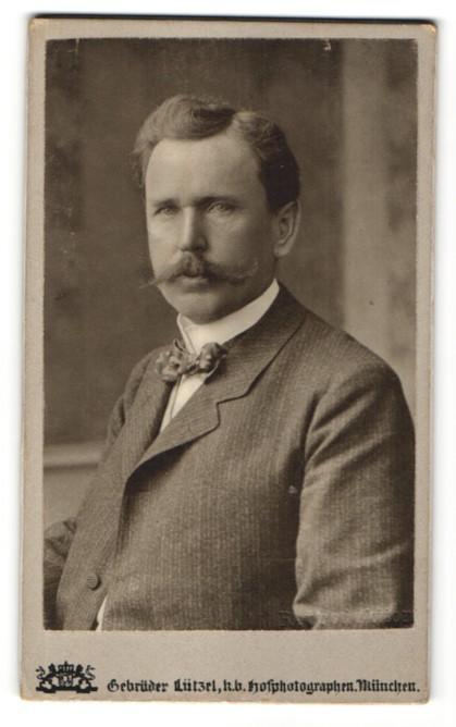 Fotografie Gebr. Lützel, München, Portrait Mann im Anzug mit Fliege