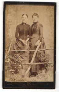 Fotografie Hans Rupprecht, Bremen, zwei wunderschöne junge Frauen in tollen Kleidern am Holzzaun stehend