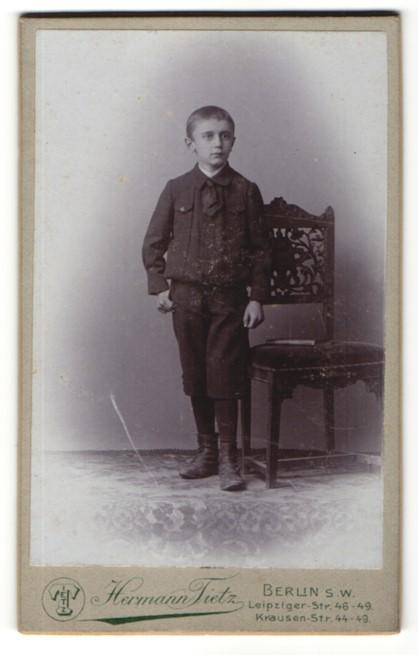 Fotografie Hermann Tietz, Berlin, Portrait frecher Bube mit kurzem Haar im hübschen Anzug