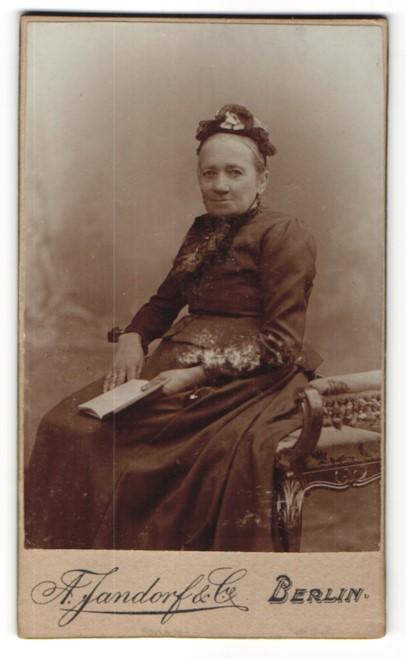 Fotografie A. Jandorf & Co, Berlin, Portrait charmant blickende ältere Dame mit Buch und Rüschenhaube