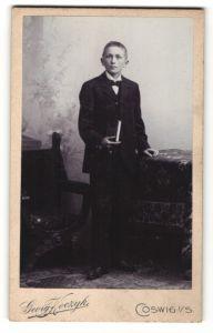 Fotografie Georg Koczyk, Coswig i. S., Portrait blonder hübscher Bube mit Buch im schwarzen Anzug