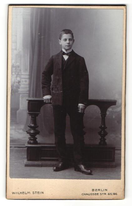 Fotografie Wilhelm Stein, Berlin, hübscher Knabe mit Fliege im eleganten schwarzen Anzug