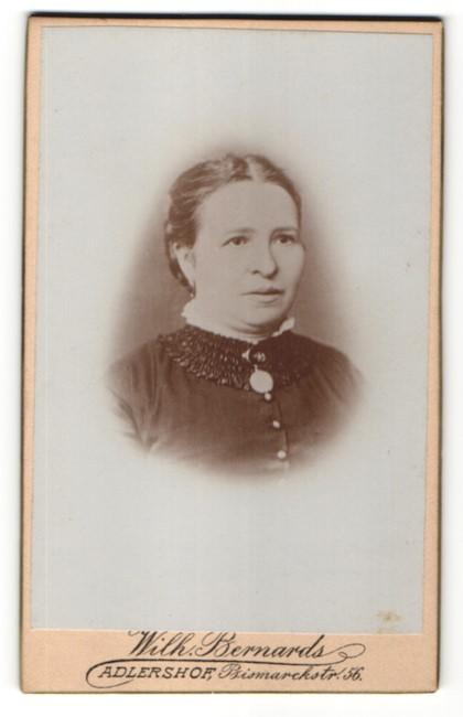 Fotografie Wilh. Bernards, Adlershof, Portrait Frau in eleganter Kleidung mit zurückgebundenem Haar