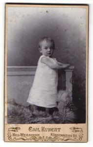 Fotografie Emil Kunert, Neu-Weissensee, Portrait Kleinkind im weissen Kleid auf einem Fellteppich