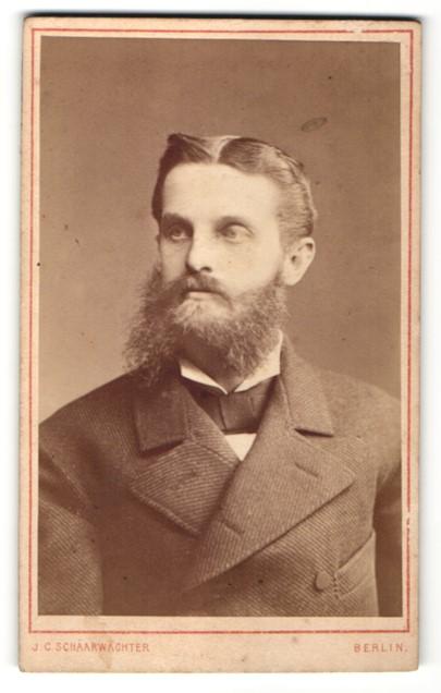 Fotografie J. C. Schaarwächter, Berlin, Portrait Mann mit Vollbart im Mantel mit Fliege