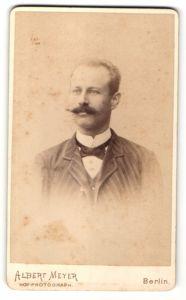 Fotografie Albert Meyer, Berlin, Portrait Mann mit Schnauzbart in gestreifter Jacke mit Fliege