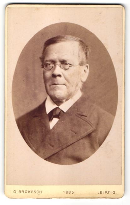 Fotografie G. Brokesch, Leipzig, Portrait Mann mit Brille in einer Jacke mit Fliege