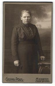 Fotografie Georg Pöltl, Miesbach, Portrait Frau in zeitgenössischer Kleidung am Tisch