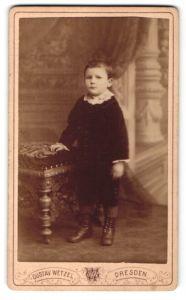 Fotografie Gustav Wetzel, Dresden, Portrait kleiner Junge im Samtanzug am Hocker