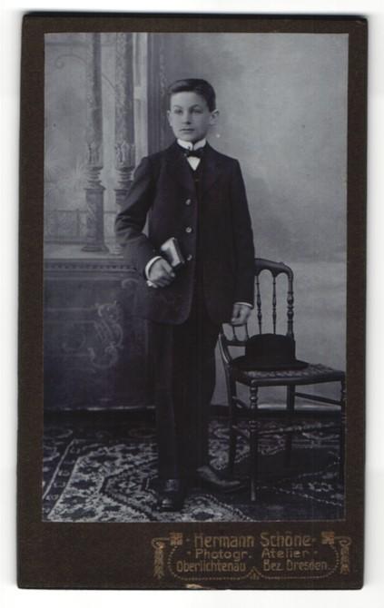 Fotografie Hermann Schöne, Dresden, Portrait Junge mit Fliege und Buch im Anzug