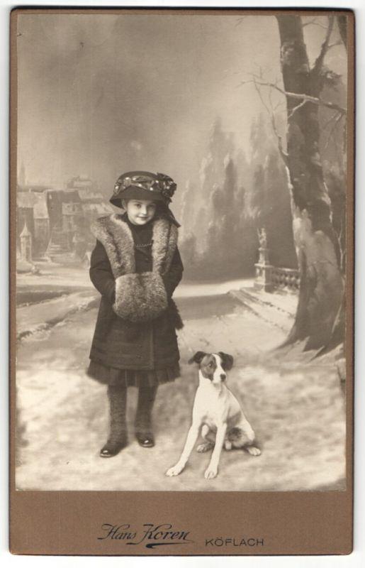 Fotografie Hans Koren, Köflach, niedliches Mädchen mit Pelzmuff & Hut nebst Hund auf verschneiter Strasse