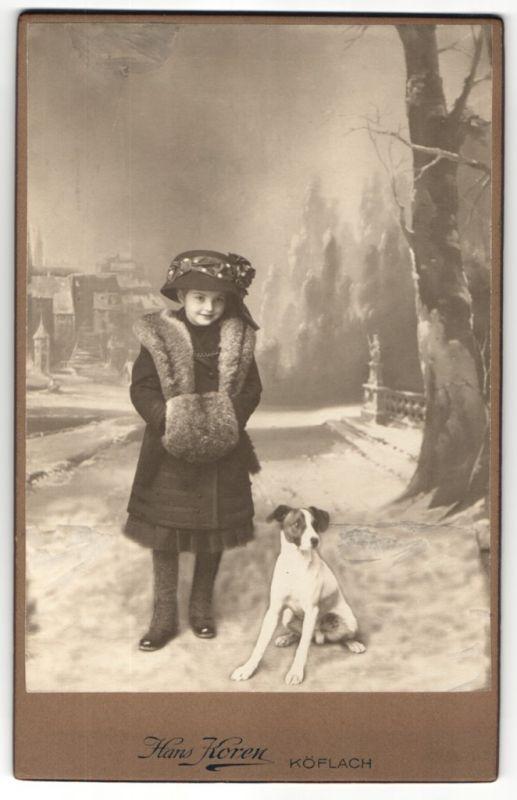Fotografie Hans Koren, Köflach, niedliches Mädchen mit Pelzmuff und Hut nebst Hund auf verschneiter Strasse