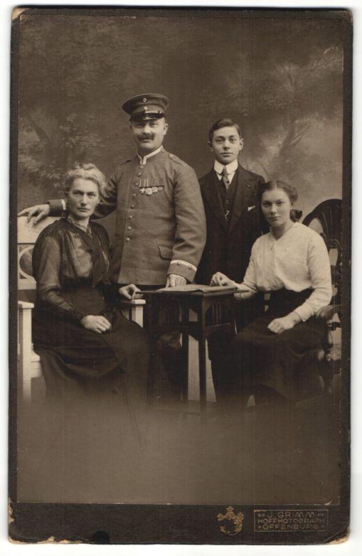 Fotografie Atelier Grimm, Offenburg, Deutscher Soldat in Uniform mit Ordenspange nebst Familie im Atelier