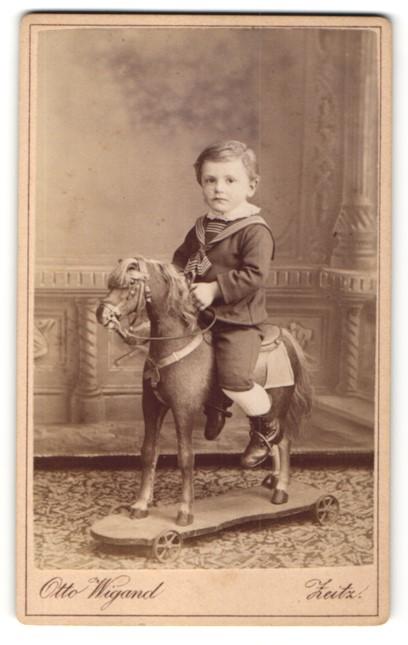 Fotografie Otto Wiegand, Zeitz, Knabe in Marineuniform auf Spielzeug-Pferd sitzend