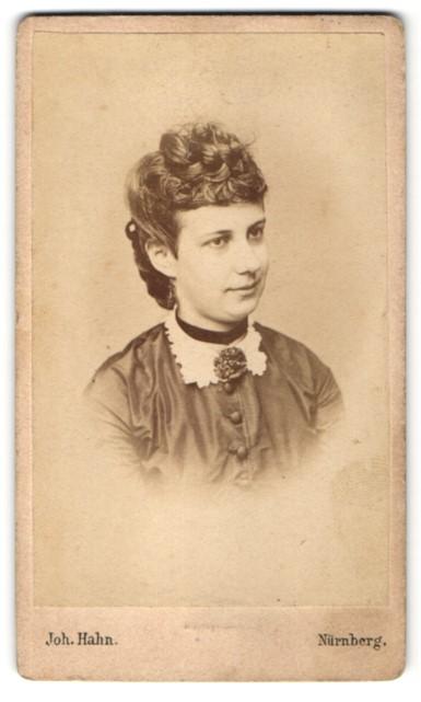 Fotografie Joh. Hahn, Nürnberg, Portrait hübsche junge Frau mit modischer Frisur und Brosche