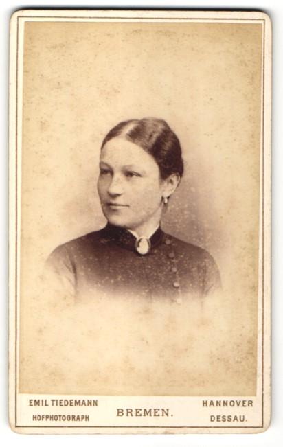Fotografie Emil Tiedemann, Bremen, Portrait charmant lächelndes Fräulein mit Ohrringen und Brosche