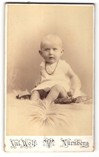 Fotografie Val. Wolf, Nürnberg, Portrait Kind sitzend auf einem Kissen