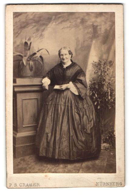 Fotografie P. S. Cramer, Nürnberg, Portrait alte Frau in weitem Kleid