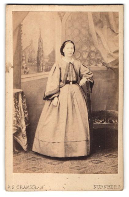 Fotografie P.S. Cramer, Nürnberg, Portrait Frau mit Mütze in weitem Kleid