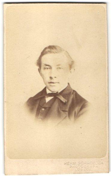 Fotografie Herm. Schröder, Lübeck, Portrait Mann mit Fliege im Anzug