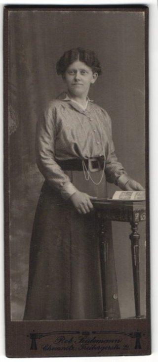 Fotografie Rob. Seidemann, Chemnitz, Portrait junge Frau mit langer Perlenkette am Tisch stehend