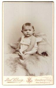 Fotografie Paul Körnig, Annaberg i. / Erzgeb., Portrait Kleinkind im weissen Hemd auf einem Fellteppich