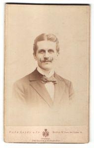 Fotografie Fritz Leyde & Co, Berlin, Portrait junger Herr mit Zwirbelbart im Anzug mit Fliege