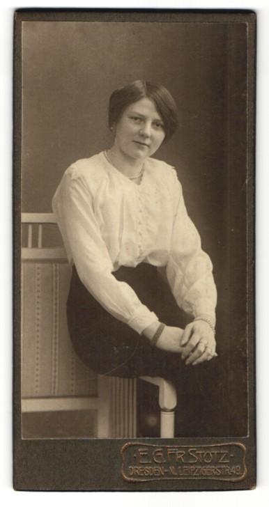 Fotografie E. G. Fr. Stotz, Dresden-N., Portrait junge Frau mit Perlenkette in weisser Bluse auf einer Stuhllehne