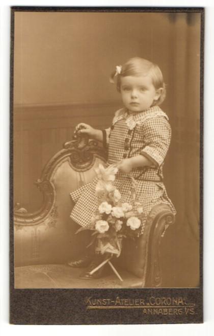 Fotografie Atelier Corona, Annaberg i. S., niedliches kleines Mädchen mit Haarschleife im karierten Kleid mit Blumenkorb