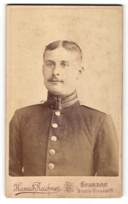 Fotografie Heinrich Reichner, Berlin-Spandau, Portrait charmant lächelnder Soldat mit Scheitel und Schnauzer in Uniform