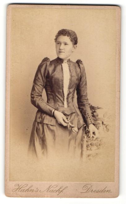Fotografie Hahn's Nachf., Dresden, charmant lächelndes Fräulein mit Blume im gerüschten Kleid