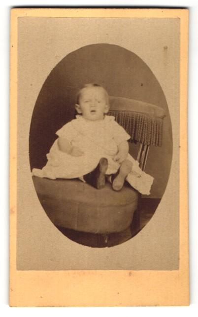 Fotografie Unbekannter Fotograf, Unbekannter Ort, Portrait Baby im weissen Kleid auf einem Stuhl