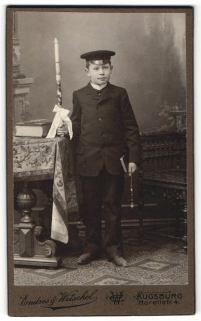 Fotografie Endres & Witschel, Augsburg, Portrait hübscher Knabe mit Schirmmütze, Buch und Kerze zur Konfirmation