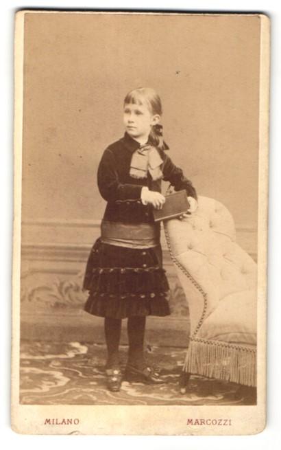Fotografie Carlo Marcozzi, Milano, Portrait blondes niedliches Mädchen mit Buch und grosser Schleife am Kragen