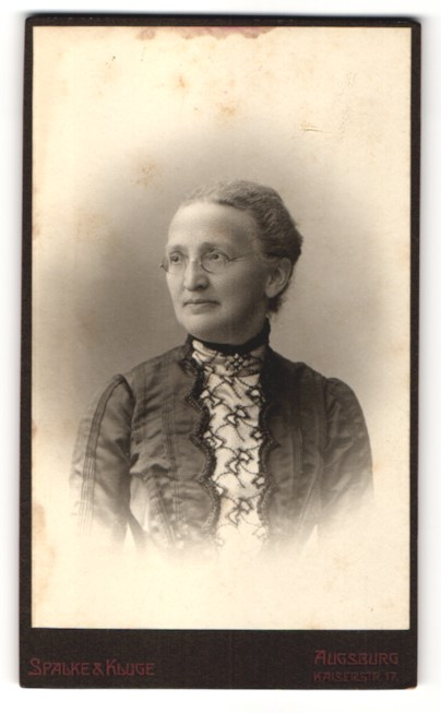Fotografie Spalke & Kluge, Augsburg, Portrait charmant blickende Dame mit Brille in elegant bestickter Bluse