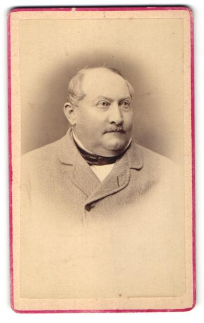 Fotografie Fotograf unbekannt, Konstanz, Portrait charmanter korpulenter Herr mit Halbglatze im grauen Jackett