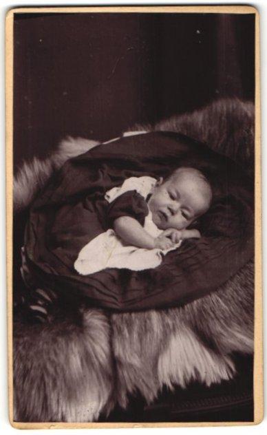 Fotografie Garralt, Dewsbury, zuckersüsses Baby im hübschen Kleidchen auf Felldecke liegend