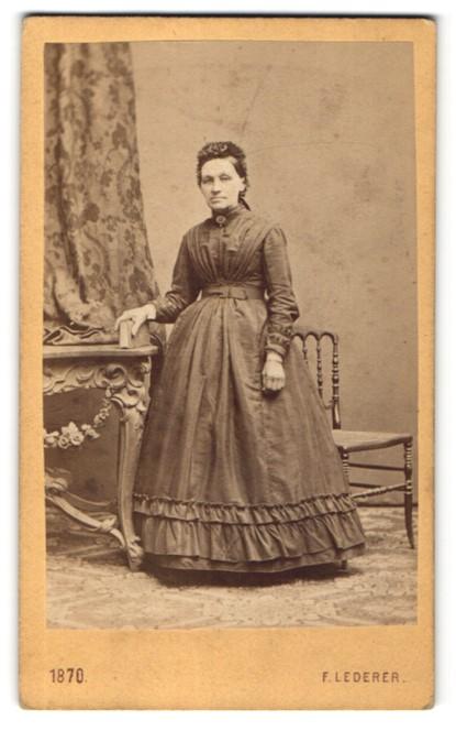 Fotografie F. Lederer, Wien, Portrait charmante Dame im prachtvollen Rüschenkleid und Buch in der Hand