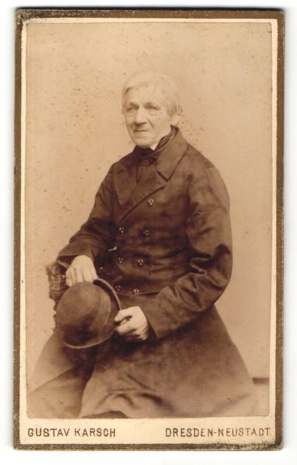 Fotografie Gustav Karsch, Dresden-Neustadt, Portrait charmanter betagter Herr mit grauem Haar und Hut im Mantel
