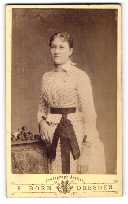 Fotografie E. Born, Dresden, Portrait charmant lächelndes Fräulein im geblümten Kleid mit Schleife 0