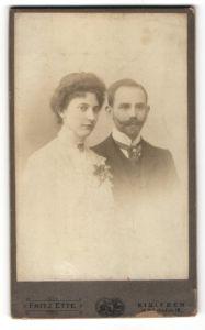Fotografie Fritz Ette, Eisleben, Portrait junges charmantes Paar in hübscher Kleidung mit Ansteckblume