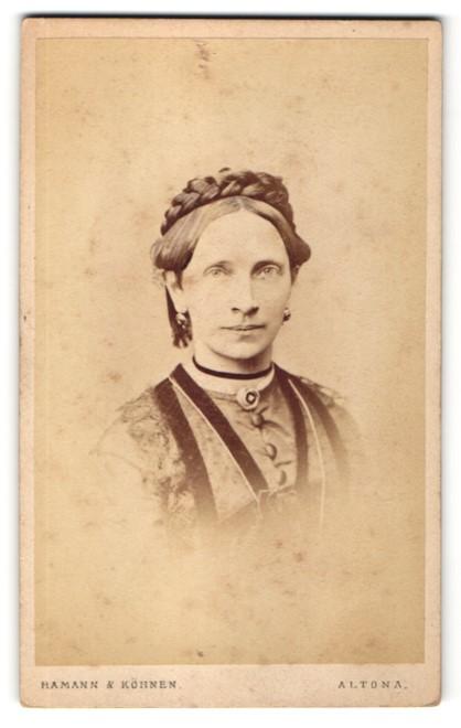 Fotografie Hamann & Köhnen, Hamburg-Altona, Portrait hübsche Dame mit Flechtfrisur, Ohrringen und Brosche 0