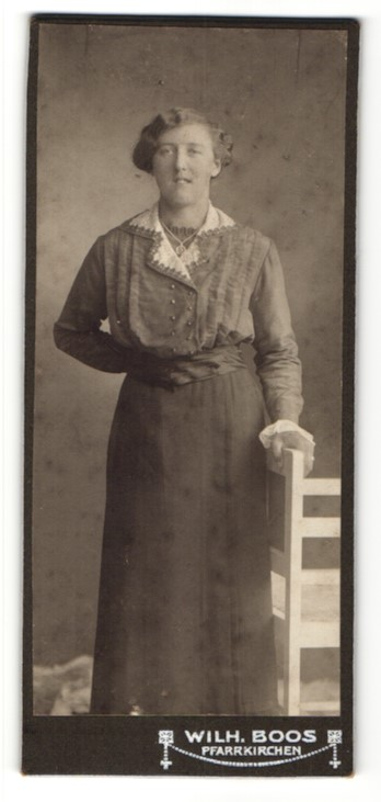 Fotografie Wilh. Boos, Pfarrkirchen, Portrait lächelnde junge Frau in interessantem Kleid mit Halskette