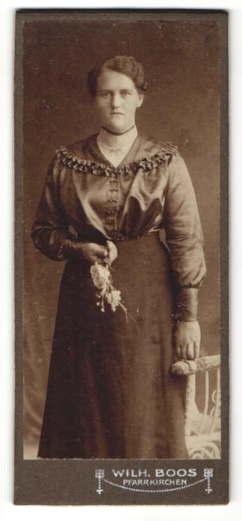 Fotografie Wilh. Boos, Pfarrkirchen, Portrait hübsche junge Frau mit Blume im gerüschten Kleid