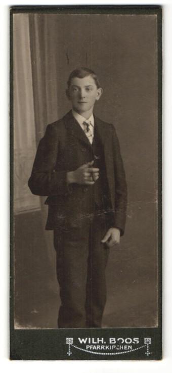 Fotografie Wilh. Boos, Pfarrkirchen, Knabe mit brünettem Haar und Zigarillo im Anzug
