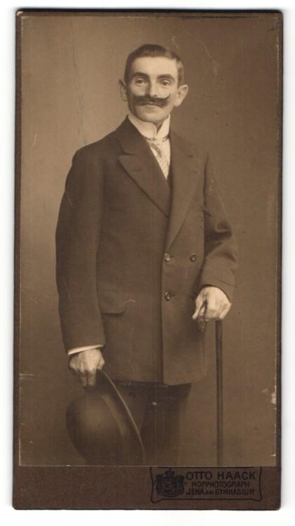 Fotografie Otto Haack, Jena, lächelnder Herr mit Oberlippenbart und Melonenhut im Mantel 0