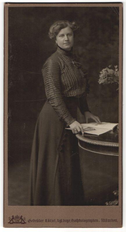 Fotografie Gebr. Lützel, München, Dame betrachtet einen Katalog im Foto-Atelier 0