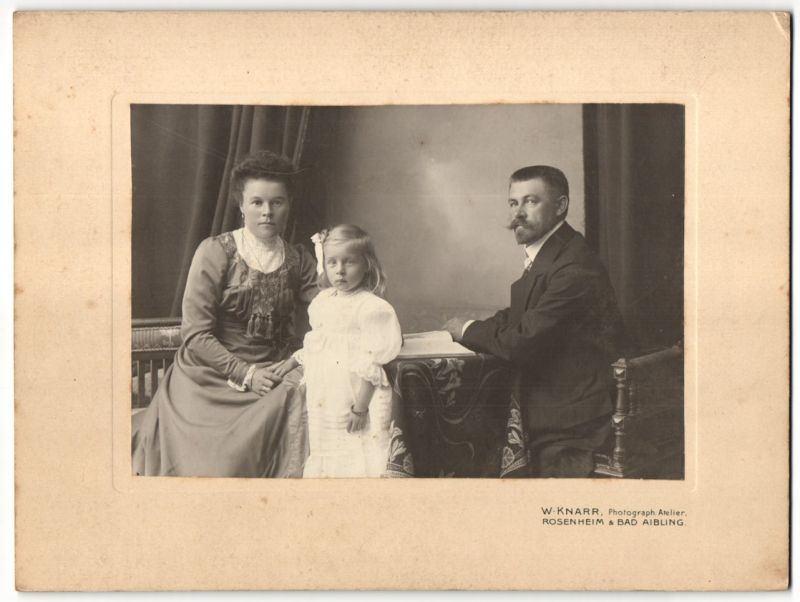 Fotografie W. Knarr, Rosenheim, Ehepaar im feinen Zwirn nebst Tochter im weissen Kleid