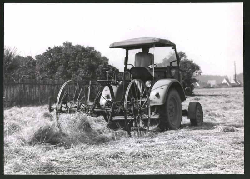 Fotografie Traktor, Landwirt steuert Schlepper über einen mit Heu bedeckten Acker 0