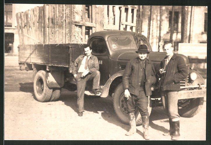 Fotografie Lastwagen, Mann posiert lässig an LKW-Pritsche